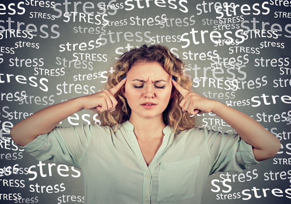 """woman looking stressed with the word """"stress"""" surrounding her"""