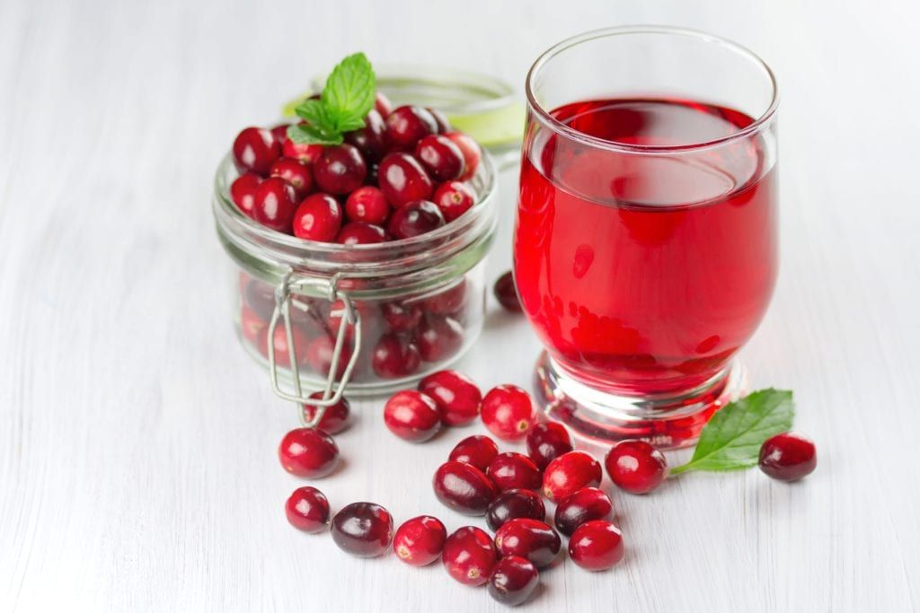 glass of cranberry juice surrounded by cranberries